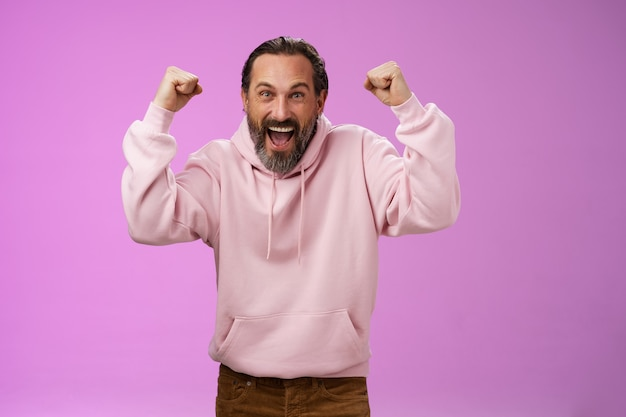 Excited cheering devoted male bearded grey hair yelling supportive words win lottery place good lucky bet standing pleased triumphing say yes raising fists victory success gesture, purple wall.