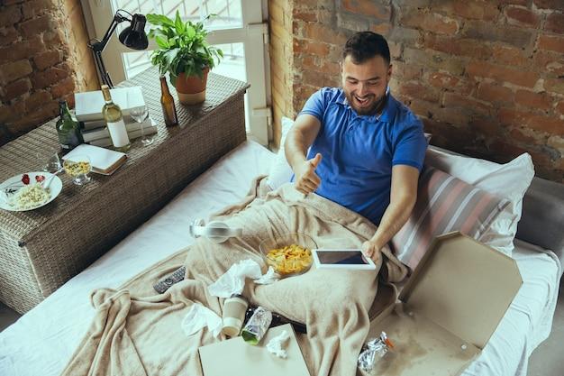 스포츠팀의 들뜬 환호, 엄지척. 지저분한 침대에 둘러싸인 게으른 남자. 행복하기 위해 나갈 필요가 없습니다. 가제트 사용, 영화 및 시리즈 감상, 감정. 패스트 푸드.