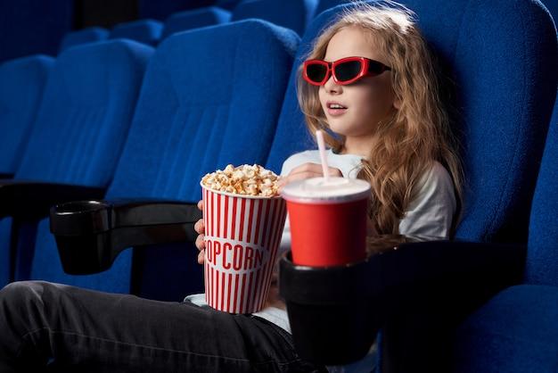 Возбужденный ребенок запечатлен с интересным фильмом в кинотеатре