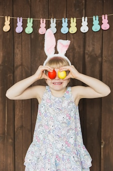 Excited child covering eyes with easter eggs