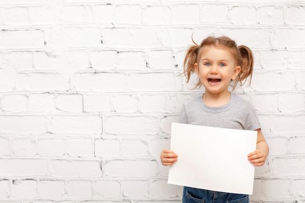하얀 빈 종이 시트를 들고 흰색 벽돌 벽에 흥분된 아이