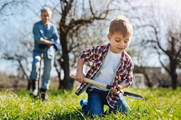 Excited child wearing a red plaid shirt standing on knees and scooping the ground while having fun with his grandfather standing behind