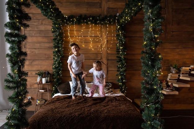 크리스마스 날 가족 오픈 선물로 집에서 부모의 침대에 뛰어드는 흥분된 아이들