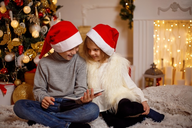 Excited children near christmas tree