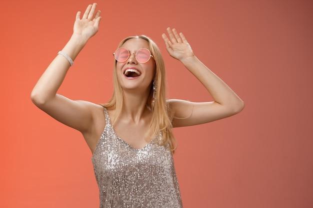 Возбужденная пугающая энергичная молодая блондинка в серебряных стильных блестящих солнечных очках платья поднимает руки вверх, весело танцует на танцполе, в ночном клубе, устраивает вечеринку, празднует день рождения, красный фон.