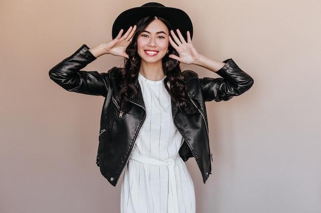 カメラを見て黒い帽子をかぶった興奮した中国人女性。笑顔でポーズをとる革のジャケットの素晴らしいアジアのモデルの正面図。