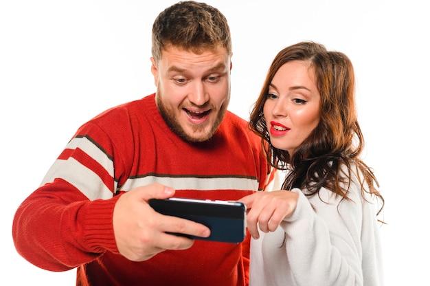 Возбужденные новогодние модели смотрят на телефон