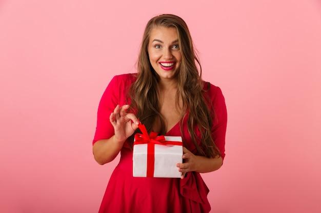 웃 고 선물 상자를 들고 빨간 드레스를 입고 흥분된 통통한 여자 20 대