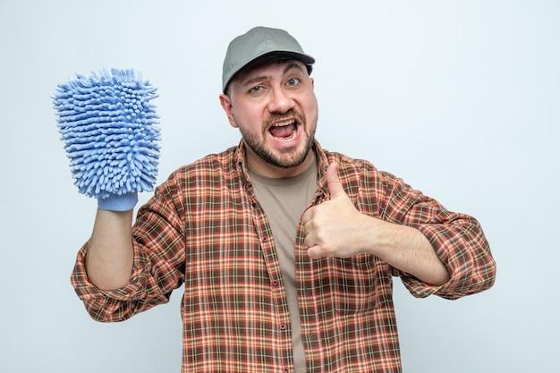 Uomo delle pulizie eccitato che tiene in mano un guanto di pulizia in microfibra e fa il pollice in alto