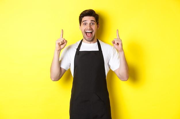 Eccitato proprietario della caffetteria in grembiule nero che punta le dita in alto, mostrando offerte speciali, in piedi su sfondo giallo.