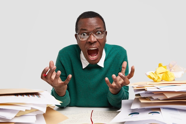 Excited confused dark skinned man gestures angrily and exclaims in annoyance, poses at desktop, cant understand difficult information, does paperwork