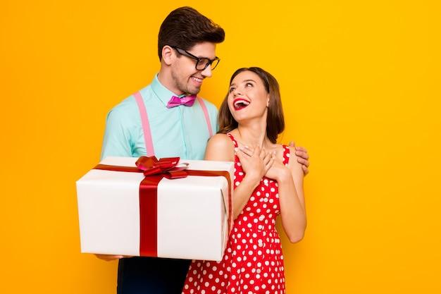 興奮したカップルのボーイフレンドがガールフレンドに大きな楽しいプレゼントを与える