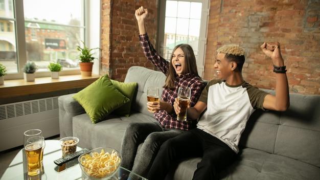 自宅でスポーツの試合のチャンピオンシップを見ている興奮したカップルの友人