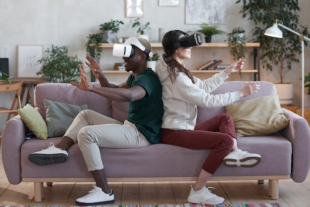 Excited couple of gamers in vr glasses sitting on sofa and playing virtual reality game in the room