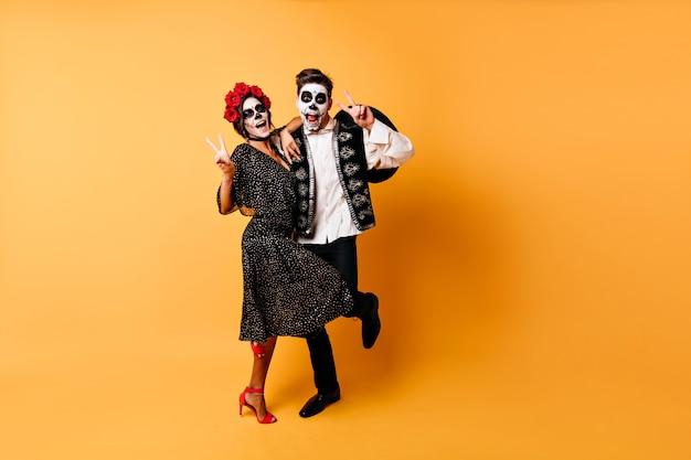 Coppia eccitata in costumi di halloween che esprimono emozioni positive.