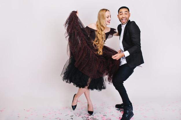 楽しんで恋に興奮したカップル。ポジティブな表現、笑顔、ダンス、笑いの高級イブニング服。