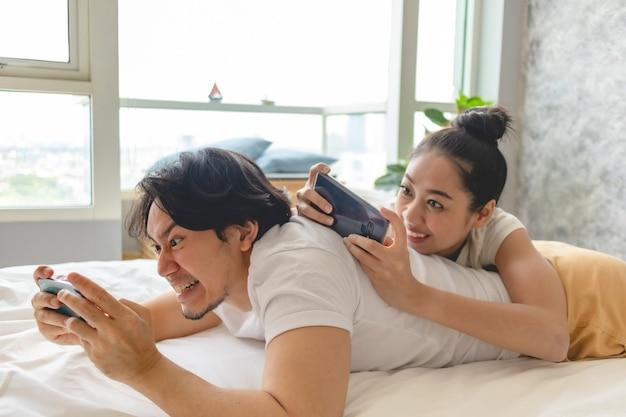 興奮したカップルがアパートで一緒に携帯電話を遊んでいます。
