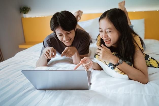 Взволнованная пара смеется на кровати, используя ноутбук дома в спальне вместе