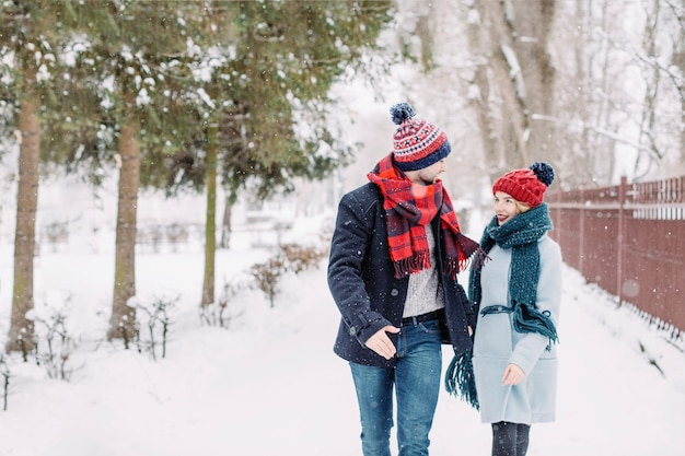 Excited couple in love running in snowfall