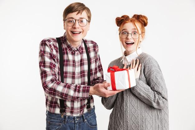 プレゼントボックスを与える学校のオタクの興奮したカップル