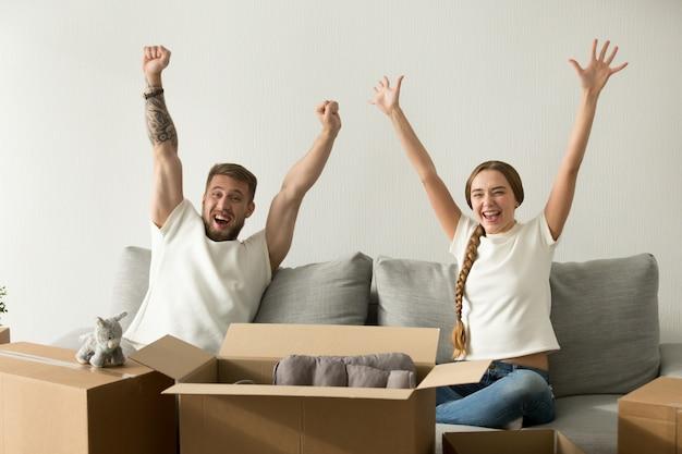 興奮しているカップルは新しい家に移動して幸せな手を上げて