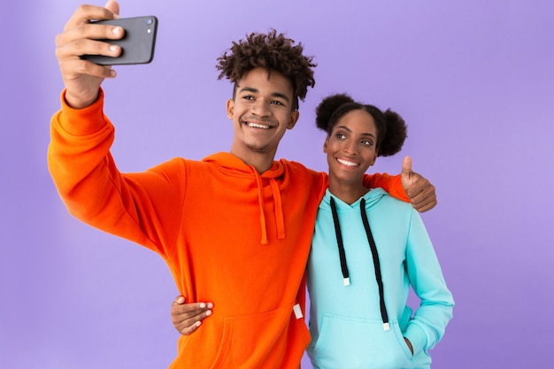 Excited couple wearing colorful sweatshirts taking selfie on smartphone, isolated over violet wall