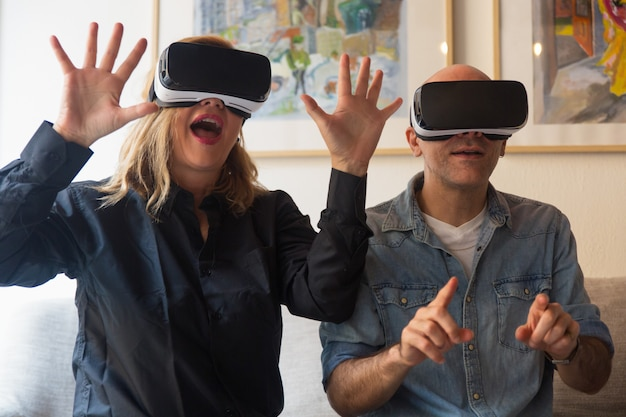 Excited couple wearing vr headset, shouting