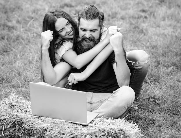 外のノートと興奮したカップル。テクノロジーとモバイルデバイス、ビジネスと教育、仕事と旅行、ソーシャルネットワーク、オンラインでの購入。良い賭け、オンライン宝くじ