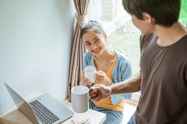 Взволнованная пара работает вместе с ноутбуком, сидя у окна утром