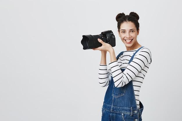 Взволнованная творческая женщина-фотограф снимает на камеру, забавляясь во время фотосъемки