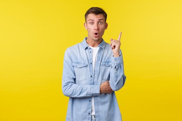Возбужденный творческий сотрудник мужского пола предлагает предложения, выражает свою точку зрения во время офисной встречи. красивый парень поднимает указательный палец в жесте эврики, громко произнося свою идею на желтом фоне.