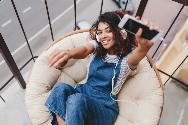 Excited curly girl in denim dress lies on soft big pillow and enjoying music in morning