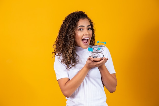 Excited curly hair woman on shopping concept. young woman with a miniature cart. e-commerce and business. shopping cart. buyer woman. yellow background.