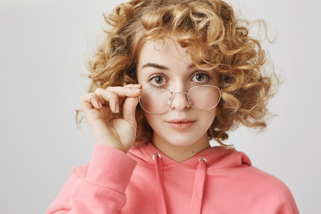 Excited curly-haired girl looking interested in glasses