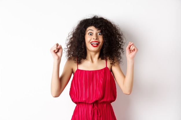 Excited curly-haired woman with evening makeup, gasping fascinated, raising hands up and rejoicing, winning prize and celebrating, standing against white background.