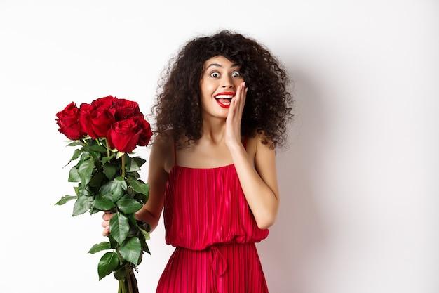 赤いドレスを着て興奮した巻き毛の女性は、バラの花束を受け取り、白い背景の上に立って、ロマンチックな贈り物を喜んで、驚きに見えます。