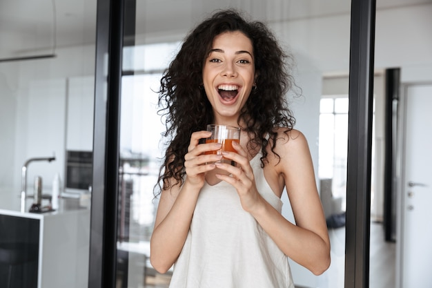 Excited curly woman with long dark hair smiling at you, while holding glass of orange juice in flat