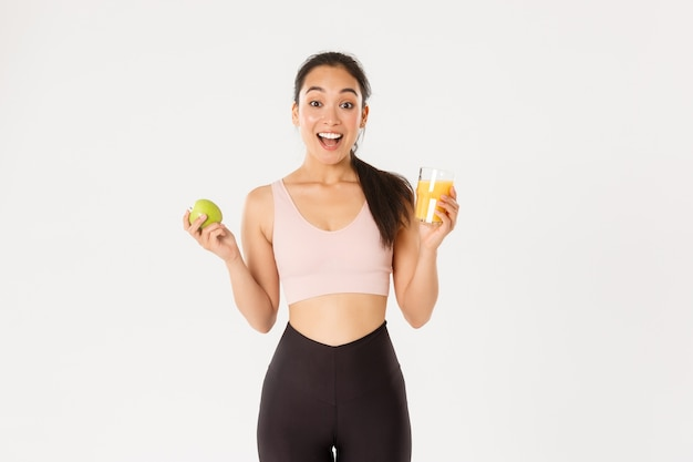 Возбужденная милая азиатская фитнес-девушка, спортсменка с задыхающимся яблоком и апельсиновым соком, изумленная и счастливая, ест здоровую, чтобы оставаться в форме, белый фон.