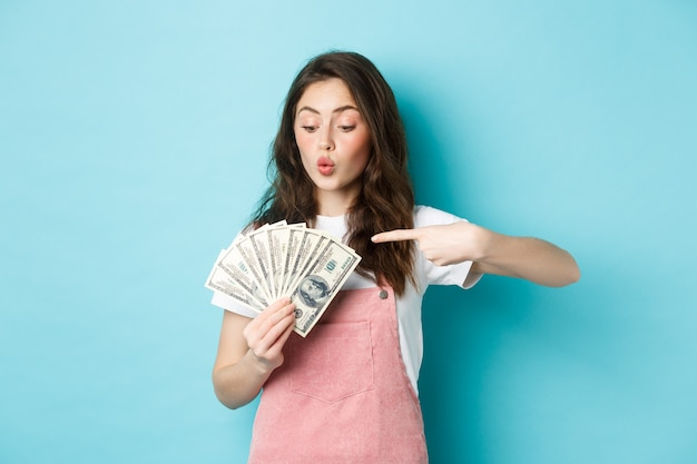 Excited cute girl holding money and pointing at dollar bills, going on shopping, standing over blue background.