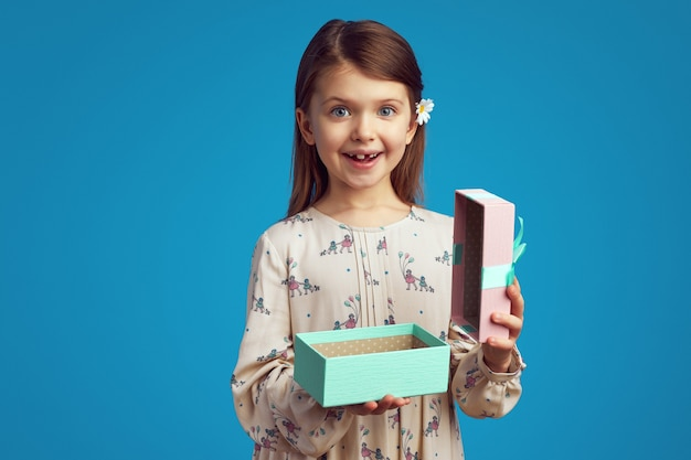 Возбужденная милая девушка держит открытую подарочную коробку, изолированную на синем фоне