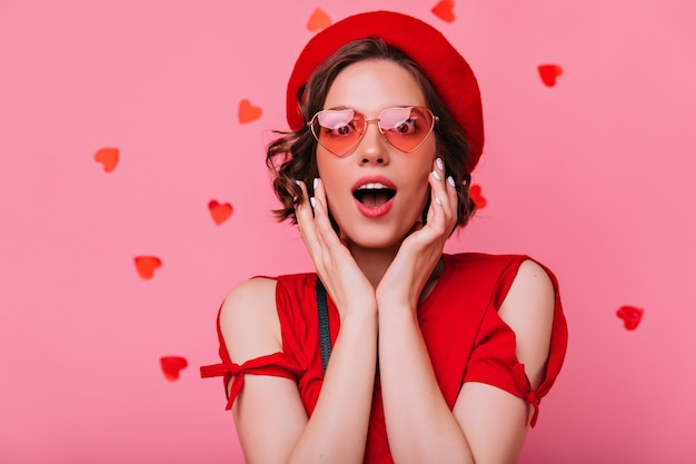 Excited cute girl posing with mouth open. indoor shot of brunette lady in red beret.