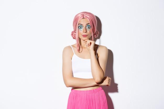 Eccitata ragazza carina festa con parrucca rosa e trucco di halloween, guardando con interesse alla telecamera, ascoltando qualcosa, in piedi.