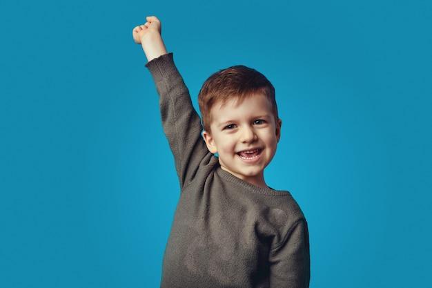 Возбужденный милый школьник стоит с поднятой рукой на синем фоне
