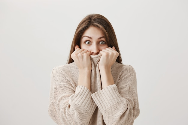 Excited cute woman pull sweater on face and looking with temptation
