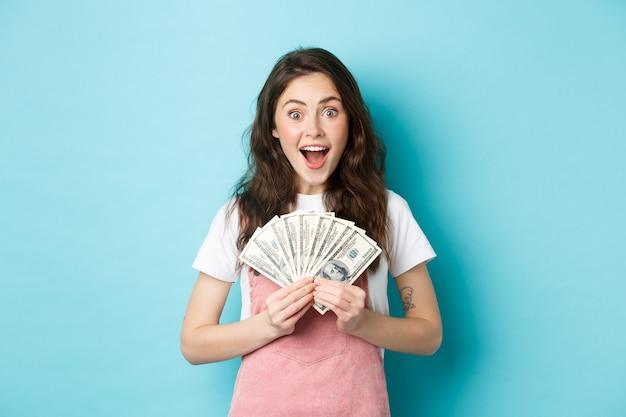 興奮したかわいい女性がお金を稼ぎ、ドル紙幣を持って、驚いて笑って、青い背景の上に立って、速い信用を得ました。