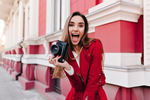 Eccitata ragazza dai capelli scuri in giacca rossa divertendosi con la macchina fotografica