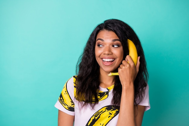 Excited dark skin girl call phone banana look empty space wear pink t-shirt isolated on turquoise color background