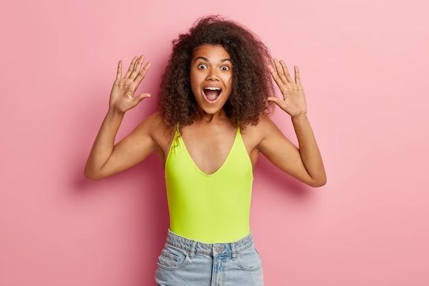 Возбужденная темнокожая афро-женщина поднимает ладони, носит яркий топ и джинсовые шорты, держит рот широко открытым.