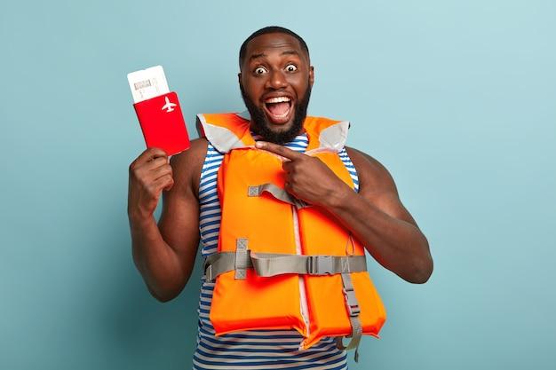 Eccitato ragazzo dalla pelle scura indica il passaporto con i biglietti, ha un viaggio inaspettato all'estero, indossa un giubbotto di salvataggio di sicurezza, ha braccia muscolose