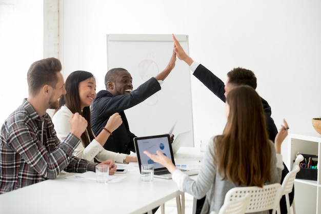 Excited diverse colleagues or partners giving high-five at team meeting
